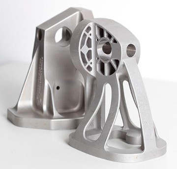 3D printed parts, like this prototype of an optimized Airbus A380 bracket made of stainless-steel powder (right) as a replacement for the standard cast steel bracket (left), could save airplanes significant weight and therefore fuel costs, argues Northwestern University case study. (Photo credit: Airbus Group Innovations)